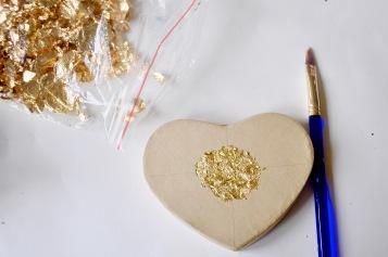 Use Mod Podge or Elmer's glue to apply the gold leaf